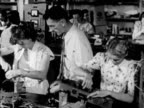 Inside British television company w/ male female workers assembling radio television sets man using plane tool planing on table man adjusting lathe...