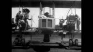 Inside plane factory during WWI / male workers fit metal plane bodies together / female workers add cloth to metal frame / body fitted together /...