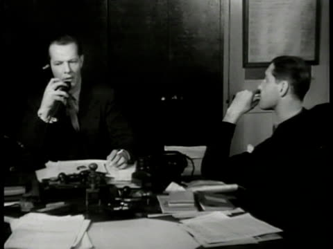 MS 'Inspector Finch' and 'Lt Roberts' at desk answering telephone Scotland Yard VS 'Finch' on phone 'well keep close to him' 'Finch' placing phone...