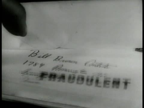 Inspector stamping envelopes w/ 'Fraudulent' stamp MS Male hands stamping envelopes in pile w/ 'Fraudulent' stamp