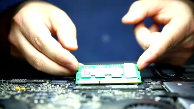 Installing RAM memory chip in laptop motherboard.