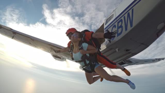 POV-Instructor und Frau in Tandem-Sprung aus Flugzeug