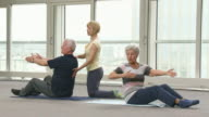 HD: Instructor Assisting Senior Couple Exercising