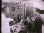 Instructor cadets in classroom looking over chart at panels in workshop room w/ turbine jet engine looking over engine Fairchild Hall Colorado Co...