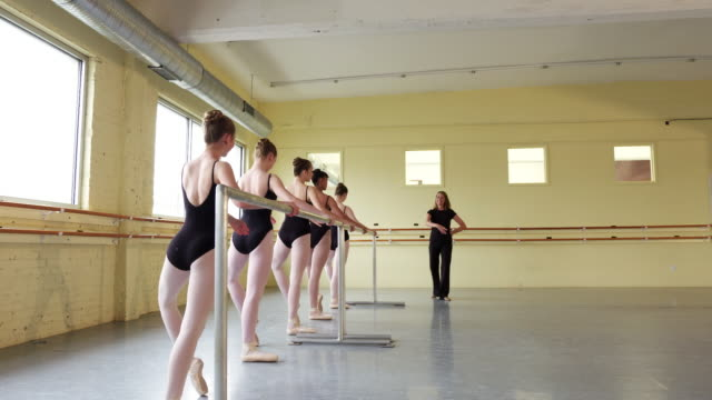 Instructor coaching ballerinas at the barre
