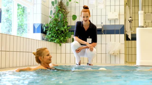Instructeur stimuleren vrouw zwemmen in zwembad