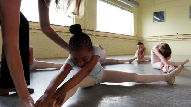 Instructor leading preteen ballerinas in practicing their form