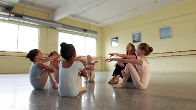 Instructor leading preteen ballerinas in warm ups