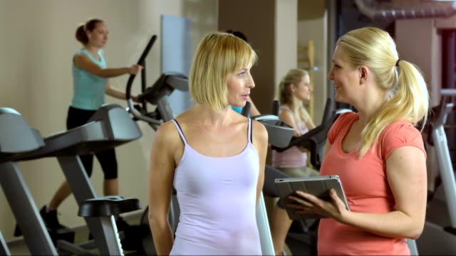 Instructor Showing Exercises On Digital Tablet