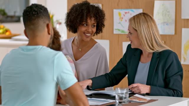 Insurance agent advising multi ethnic family at home