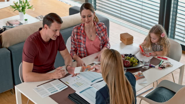 Insurance agent handing a brochure to couple in their house
