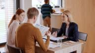 Verzekeringsagent schudden handen met een paar op een bijeenkomst in hun huis