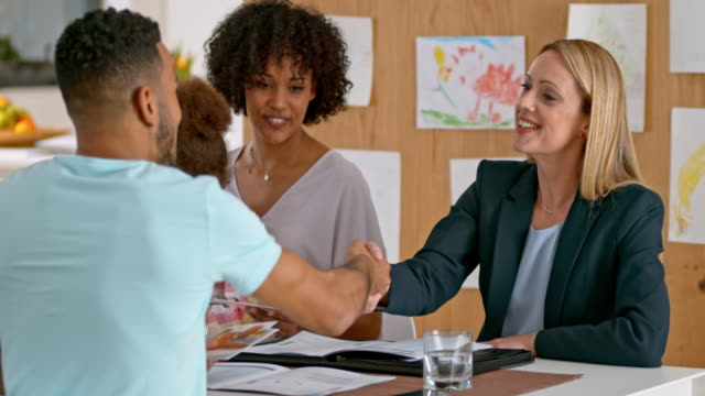 Insurance agent shaking hands with a multi ethnic couple at a meeting in their home