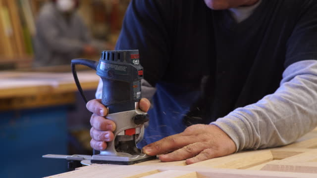 ECU of intense facial expression of worker operating hand-held sander to smooth surface of custom wood windows