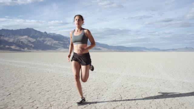 SLO MO : Intense Woman Running through Desert