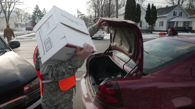 Interior and exterior shots of National Guard soldiers distributing emergency bottled water supplies to the residents of Flint due to the local water...