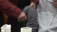 Interior anon anonymous shots of older elderly people in a care home wrinkly hands stirring tea care worker helping man to remove his coat from his...