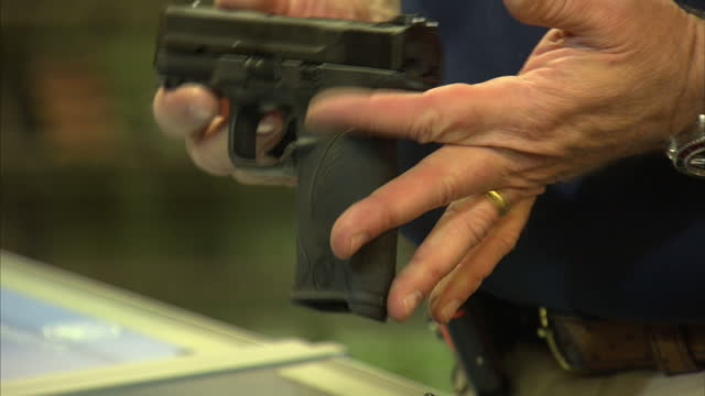 Interior close up shots of an anonymous hand holding a Smith and Wesson semi automatic handgun in a gun shop in order to explain its merits to an...