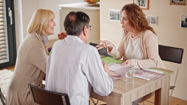 Interior designer explaining her design ideas to a senior couple in their home