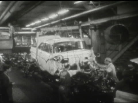 / Interior factory men move partially assembled car hanging from roof along assembly line / Lines of assembled cars on factory floor / Men punch time...