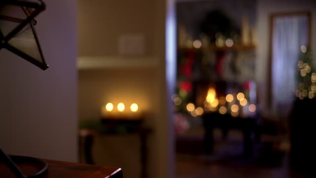 Interior living room filled with Christmas decorations including candles, evergreen, stockings hanging on a stone fireplace with burning fire, Christmas trees and wreaths shot slightly out of focus for graphics.
