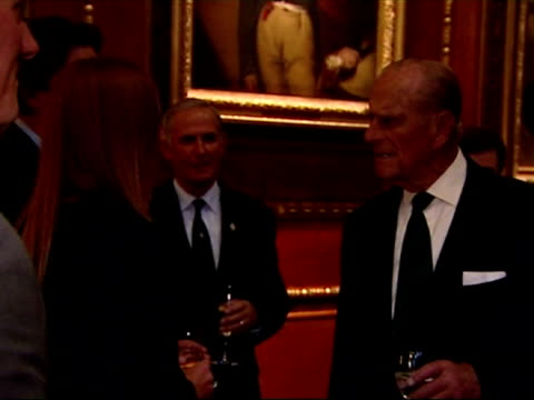 Interior medium shots Prince Philip chatting to guests at reception for the participants of the Royal Windsor Horse Show Jubilee Pageant Queen and...