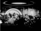 Interior nightclub performing couple can be seen dancing in front of orchestra in background also waiter and maître d' / couple sitting at table with...