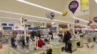 Interior of a Tesco Plc supermarket showing checkout tills shoppers bagging and paying for their groceries Conveyor belt divider promoting Tesco...