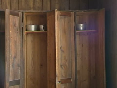 / interior of barracks pan from small wooden closets to windows