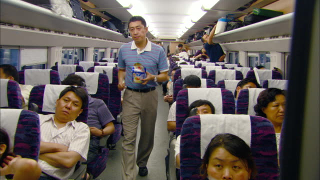 WS Interior of moving passenger train, rows filled with people, Jinan, Shandong, China