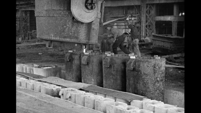Interior of steel mill steel workers pouring steel from large vat Interior steel mill men working on January 01 1930