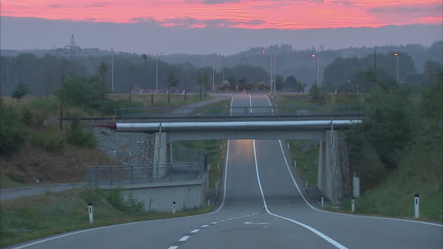 Interior point of view shots from vehicle travelling on road in Passau Germany Traffic driving along roads in early morning with red sky and various...