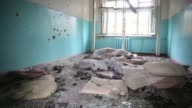 Interior room with pillows and other debris on floor of hospital destroyed when the proRussians and Ukrainian military fought a major battle in July...
