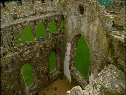Interior ruins ancient church that no longer has windows or a roof looking through window frames to green grass outside
