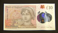 Interior setup shots new 10 pound bank notes lying on black table showing new design with Jane Austin picture
