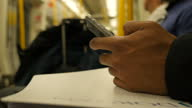 Interior shot anonymous commuter sitting on London Underground train using mobile phone on May 14 2015 in London England