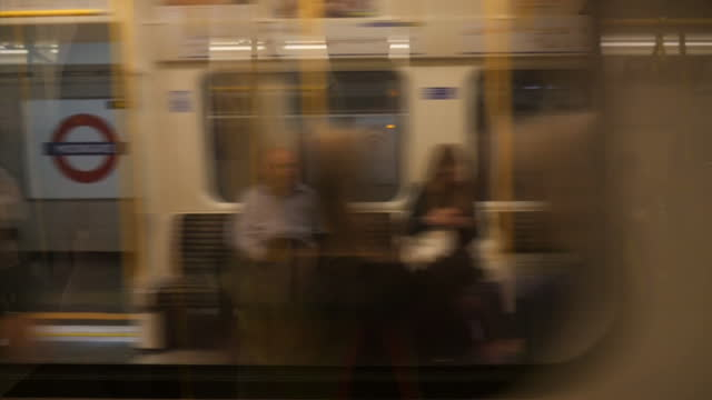 Interior shot commuters sitting on London Underground train as trains pass at station on May 05 2015 in London England