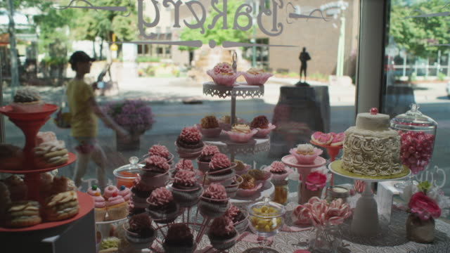 Interior shot looking out the front window of a small town bakery. Finely decorated cakes, cookies, and sweets appear in the forground; pedestrians pass in the background.