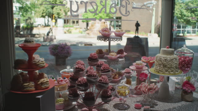 Interior shot looking out the front window of a small town bakery. Finely decorated cakes, cookies, and sweets appear in the foreground; a bicyclist and convertible pass in the background.