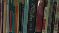 Interior shot panning shots of books on shelves on subject of anorexia eating disorders and psychology including books by Freud Close ups of books...
