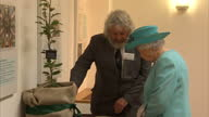 Interior shot Queen Elizabeth II visits the Royal Society of Edinburgh walks into room to look at artifacts after ceremony where medals are awarded...