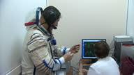 Interior shot Tim Peake wearing space suit speaking to technician looking at computer display showing suit calibration / Interior shot Tim Peake wlk...