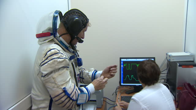 Interior shot Tim Peake wearing space suit speaking to technician looking at computer display showing suit calibration / Interior shot Tim Peake wlk...