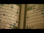 interior shots anon male hands leafing through Qu'ran interior shots various of Muslim men in mosque at prayer praying interior shots prayer books on...