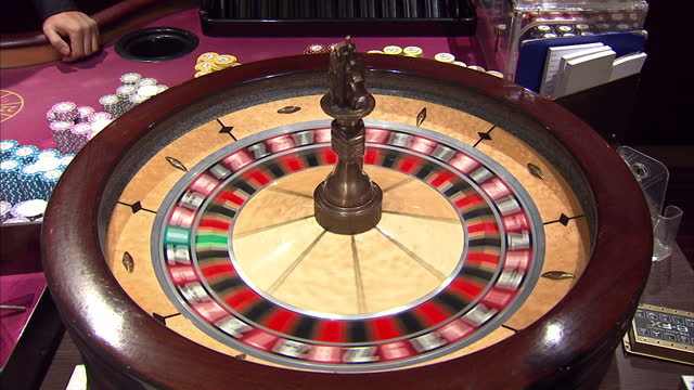 Interior shots anonymous croupier putting ball into roulette wheel spinning it around Interior close up shots red black numbers spinning on roulette...
