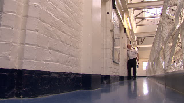Interior shots anonymous prisoners standing by cells Interior shots prison officer checking cells Anonymous Prison Interiors on December 03 2012 in...