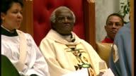 Interior shots Archbishop Desmond Tutu hugging fellow churchmen during his last service