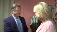 Interior shots Camilla Duchess of Cornwall meeting TV presenter Alan Titchmarsh and looks at guide dog in pen on September 09 2015 in London England