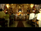 interior shots Catholic church service with cutaways of churchgoers women with fans Virgin Mary statue