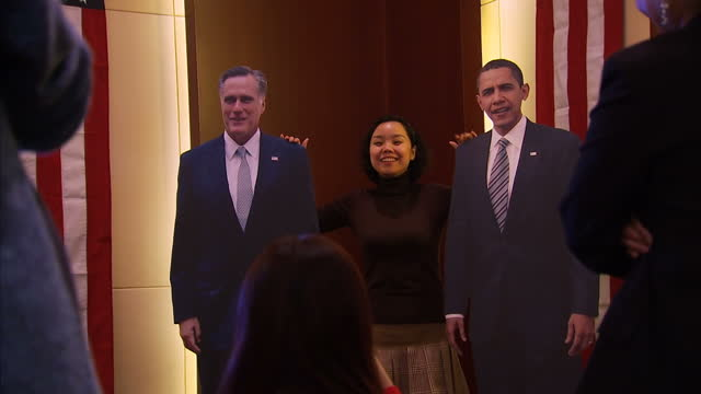 Interior shots Chinese people taking part in mock US Election polling station with residents having their pictures taken with cardboard cutouts of...